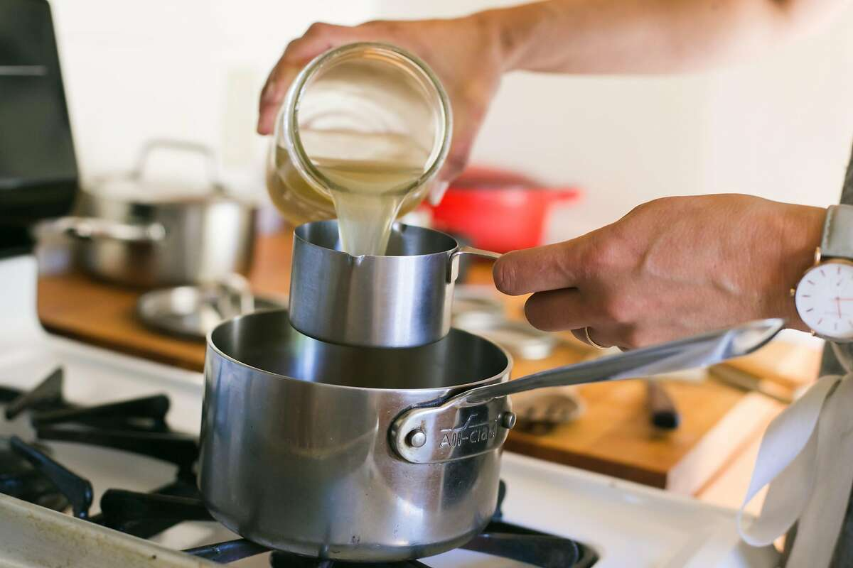 Kristen Rasmussen pours homemade chicken stock into a pot with millet for a savory porridge recipe.
