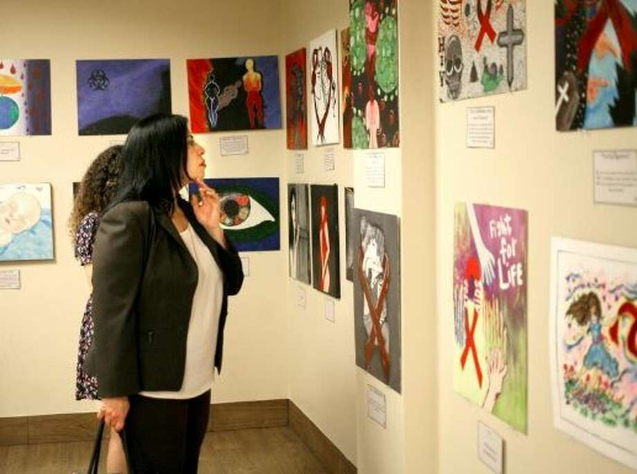 Julie Bazan, among other art enthusiasts, admiring the work by local and foreign artists during the HIV and STD awareness art contest held April 10 at the City of Laredo Health Department Auditorium. Click through this gallery to see the most and least friendly Texas cities for LGBT people. Photo: Francisco Vera/Laredo Morning Times