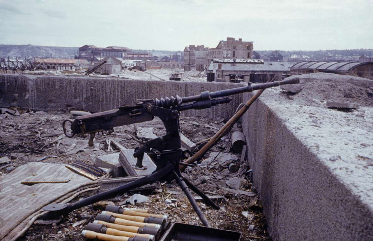 View of an abandoned German machine gun, and ammunition case on the roof of a building in the wake of the D-Day invasion by Allied forces during World War II, France, 1944.