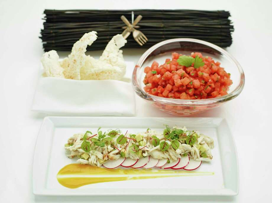 Avocado and Crab Salad is garnished with sliced radish and citrus-mango sauce, foreground; a chilled Watermelon Salad, upper right, is served with deep-fried rice crisps. Photo: Phil Mansfield, HONS / © 2017 The Culinary Institute of America - Phil Mansfield