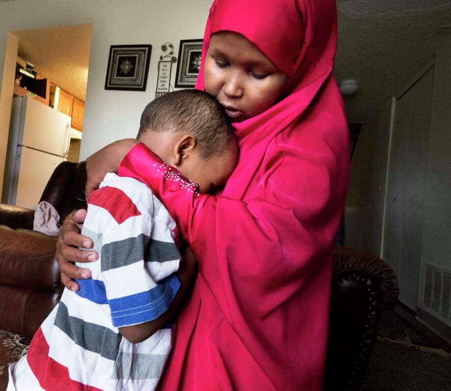 Suaado Salah comforts her 3-year-old son at their apartment in suburban Minneapolis. Luqman and his 18-month-old sister got measles during Minnesota's current outbreak. MUST CREDIT: Photo by Courtney Perry for The Washington Post / Stratford Booster Club