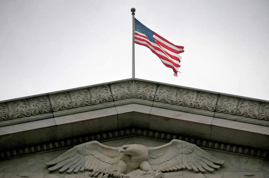 A tattered flag flies over the Rayburn House office building in NW Washington D.C. (AP Photo/Allison Shelley, The Washington Times) Photo: Allison Shelley, MBR / The Washington Times