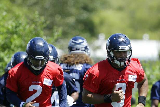 Seattle Seahawks quarterback Russell Wilson, right, and backup quarterback Trevone Boykin, left, take part in a drill during NFL football practice, Friday, June 2, 2017, in Renton, Wash. (AP Photo/Ted S. Warren)