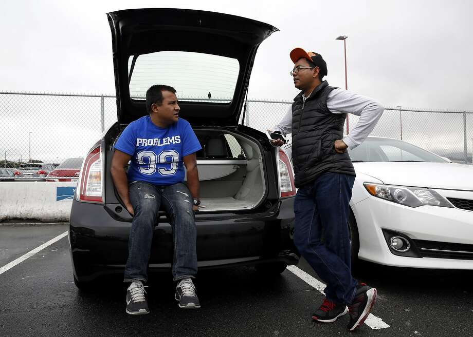 Uber drivers Madan Shrestha (left) and Om Adhikari chat while waiting for calls in the TNC lot at San Francisco International Airport in San Francisco, California, on Wednesday, March 9, 2016. Photo: Connor Radnovich Connor Radnovich, The Chronicle