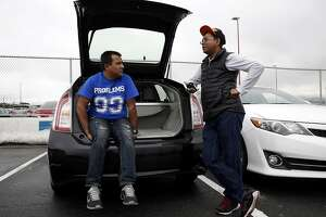 Uber drivers Madan Shrestha (left) and Om Adhikari chat while waiting for calls in the TNC lot at San Francisco International Airport in San Francisco, California, on Wednesday, March 9, 2016.
