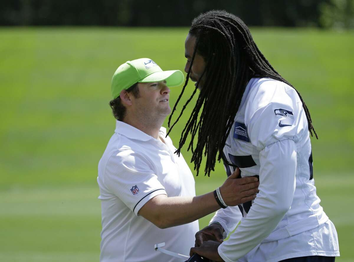 Seattle Seahawks cornerback Richard Sherman, right, moves to hug general manager John Schneider, left, following NFL football practice, Friday, June 2, 2017, in Renton, Wash. (AP Photo/Ted S. Warren)