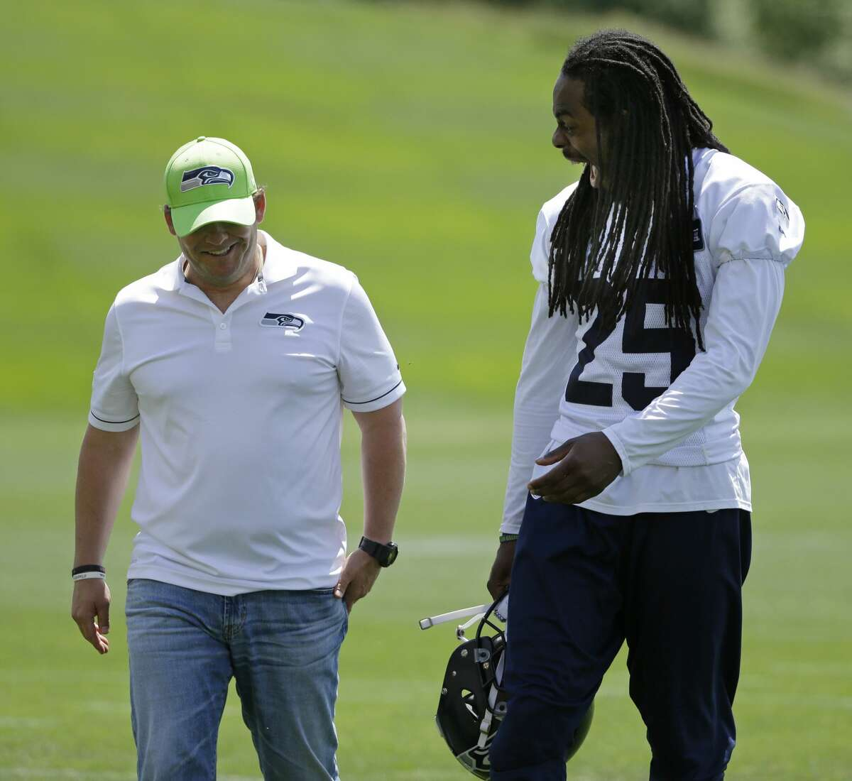 Seattle Seahawks cornerback Richard Sherman, right, laughs as he walks with general manager John Schneider, left, following NFL football practice, Friday, June 2, 2017, in Renton, Wash. (AP Photo/Ted S. Warren)