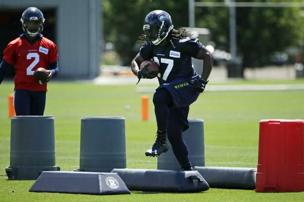 Seattle Seahawks running back Eddie Lacy, right, takes part in a drill during NFL football practice as backup quarterback Trevone Boykin (2) looks on, Friday, June 2, 2017, in Renton, Wash. (AP Photo/Ted S. Warren)