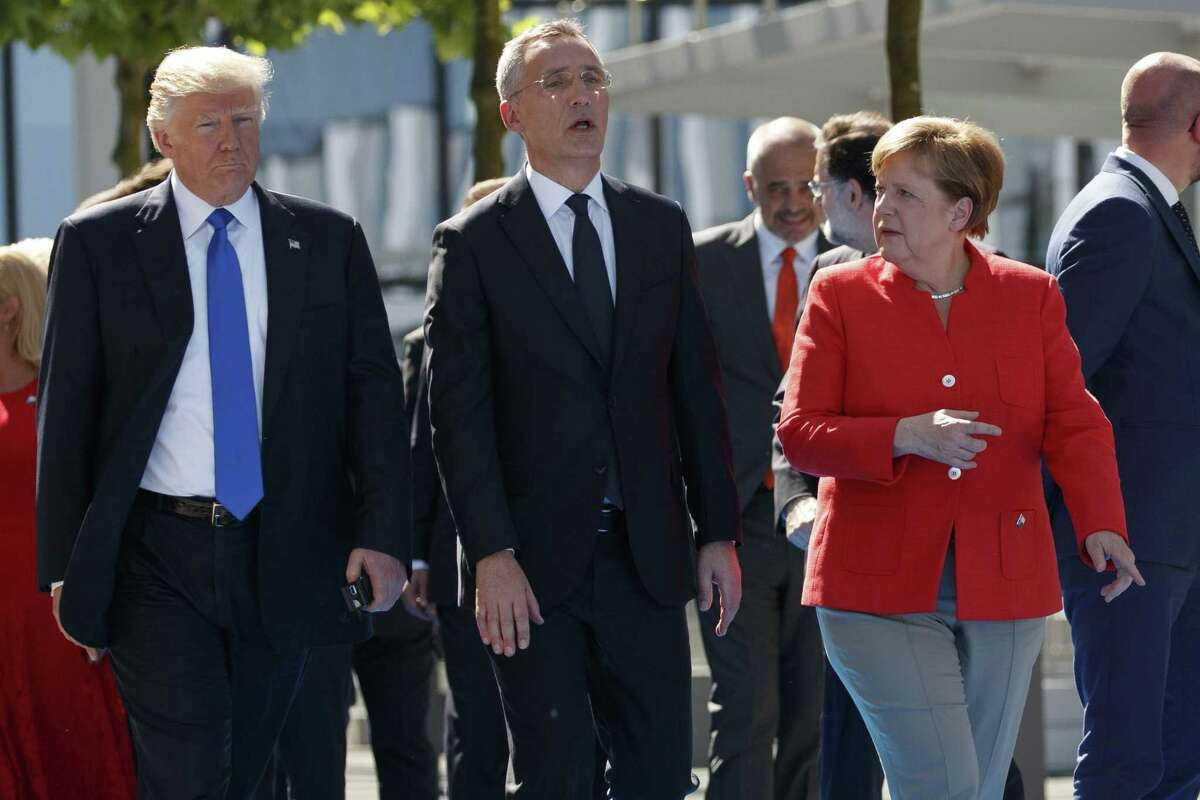 NATO Secretary General Jens Stoltenberg, center, walks with President Donald Trump and German Chancellor Angela Merkel during a ceremony to unveil artifacts from the World Trade Center and Berlin Wall for the new NATO headquarters, Thursday, May 25, 2017, in Brussels. (AP Photo/Evan Vucci)