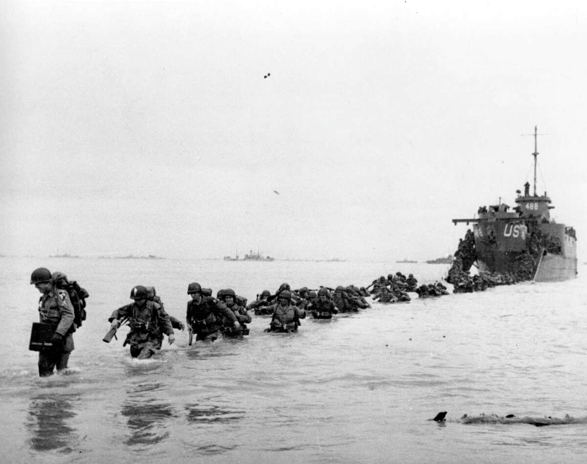 U.S. reinforcements wade through the surf from a landing craft in the days following D-Day and the Allied invasion of Nazi-occupied France at Normandy in June 1944 during World War II. (AP Photo/Bert Brandt)