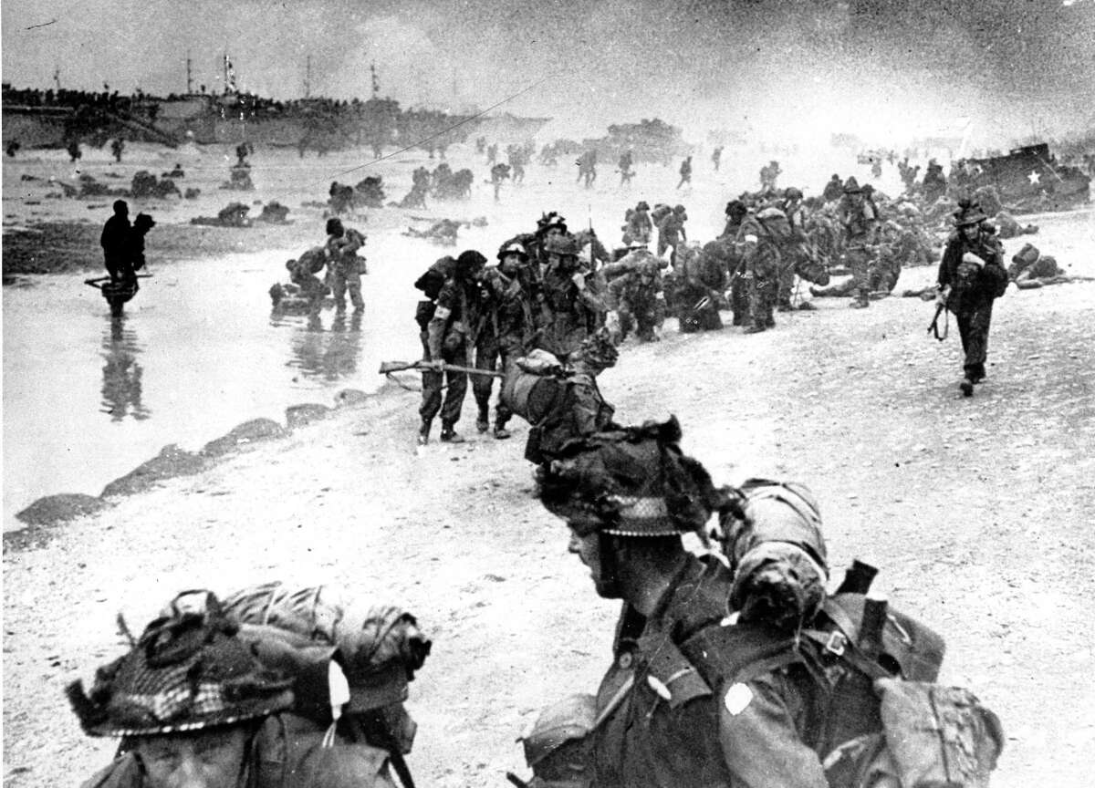 In this photo provided by the British Navy, wounded British troops from the South Lancashire and Middlesex regiments are being helped ashore at Sword Beach, June 6, 1944, during the D-Day invasion of German occupied France during World War II. (AP Photo/British Navy)