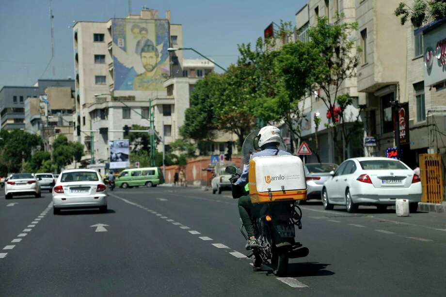A motorcycle delivery driver for the Bamilo online shopping site rides the streets of Iran's capital, Tehran. Iran remains in many ways cut off economically from the rest of the world, fueling a local tech startup scene.  Photo: Ebrahim Noroozi, STR / Copyright 2017 The Associated Press. All rights reserved.