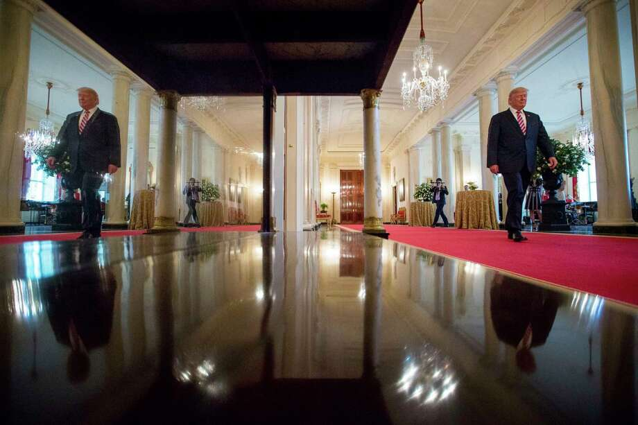 President Donald Trump, right, and seen in reflection, left, arrives for an Air Traffic Control Reform Initiative event in the East Room at the White House, Monday, June 5, 2017, in Washington. (AP Photo/Andrew Harnik) ORG XMIT: DCAH101 Photo: Andrew Harnik / Copyright 2017 The Associated Press. All rights reserved.