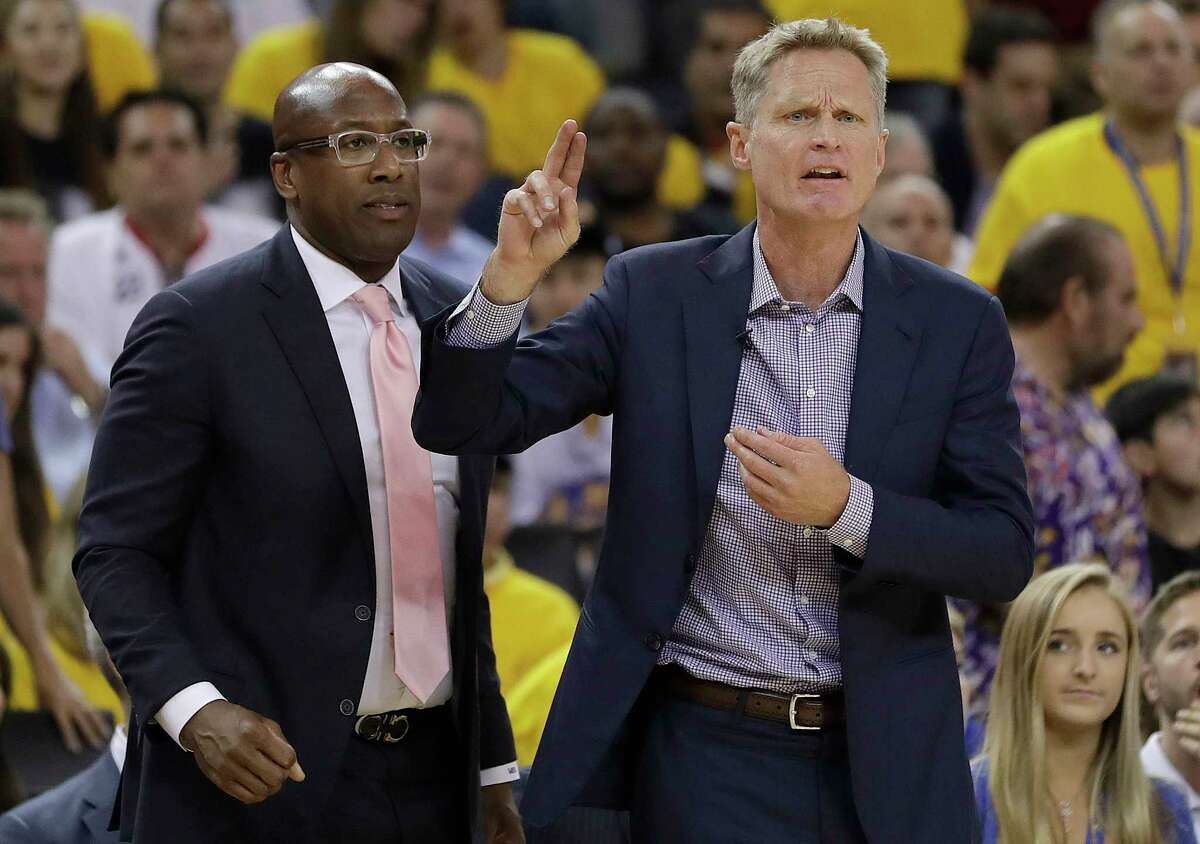 Golden State Warriors head coach Steve Kerr, right, gestures next to interim head coach Mike Brown during the first half of Game 2 of basketball's NBA Finals against the Cleveland Cavaliers in Oakland, Calif., Sunday, June 4, 2017. (AP Photo/Marcio Jose Sanchez) ORG XMIT: OAS131