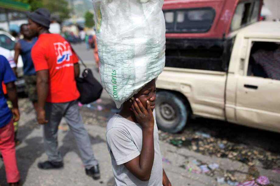 Watson Saint Fleur, 12, carries water for sale in a suburb of Port-au-Prince, Haiti.  Watson is unsure how he came to be a woman's servant.  after his mother dies.  d in hardship doing household chores and peddling plastic bags of drinking water along city streets noisy with motorbikes and trucks. (AP Photo/Dieu Nalio Chery) Photo: Dieu Nalio Chery, STR / Copyright 2017 The Associated Press. All rights reserved.