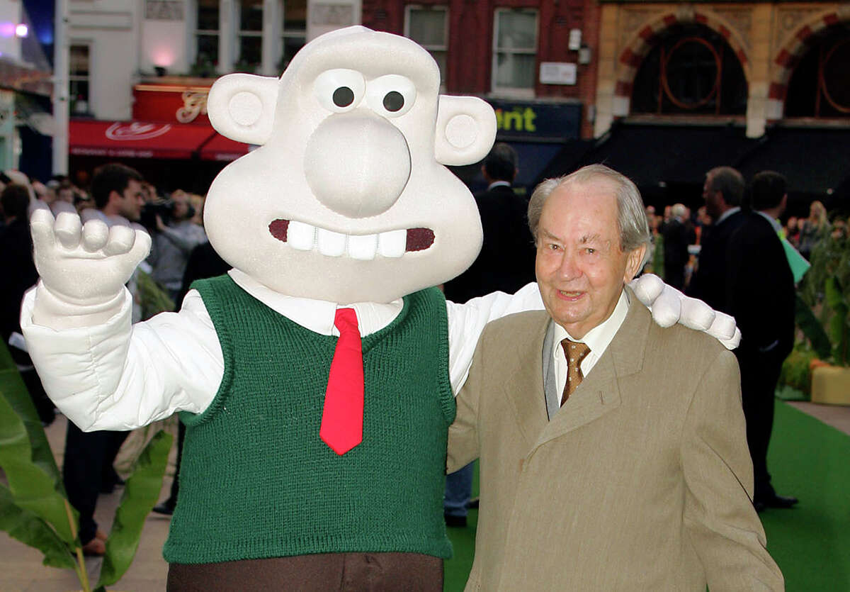 FILE - In this Sunday, Oct. 2, 2005 file photo, British actor Peter Sallis, who voices the part of Wallace poses with a person dressed as the character 'Wallace' on arrival at the Leicester Square Odeon, London for the premiere of Wallace & Grommit: The Curse of the Were-Rabbit. Sallis, who played irrepressible, cheese-loving inventor Wallace in the