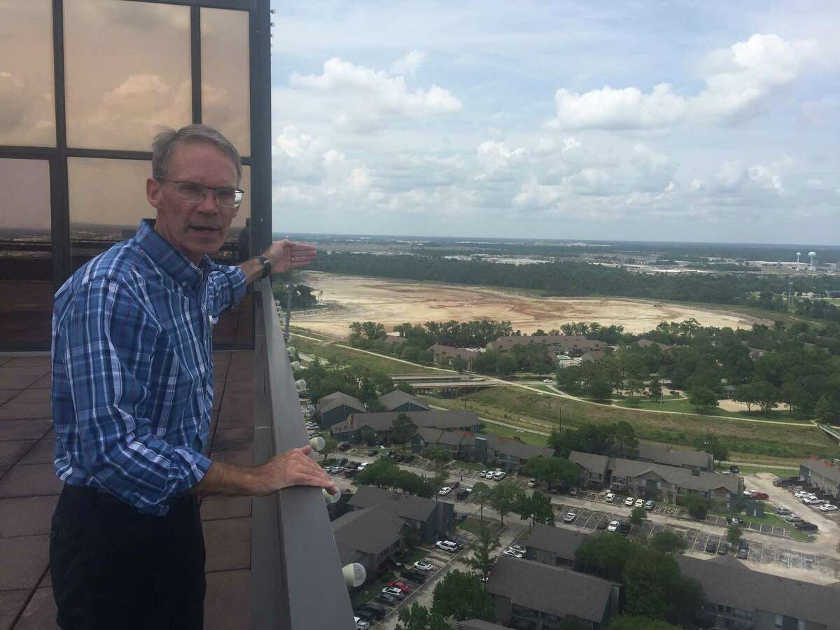 North Houston District vice president Robert Fiederlein points out the path water took in the Tax Day floods of 2016. Behind, construction advances on a 160-acre detention basin planned by the Harris County Flood Control District.