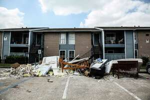 Piles of furniture and debris fill up the parking lot at Arbor Court Apartments on Tuesday, April 26, 2016. ( Elizabeth Conley / Houston Chronicle )
