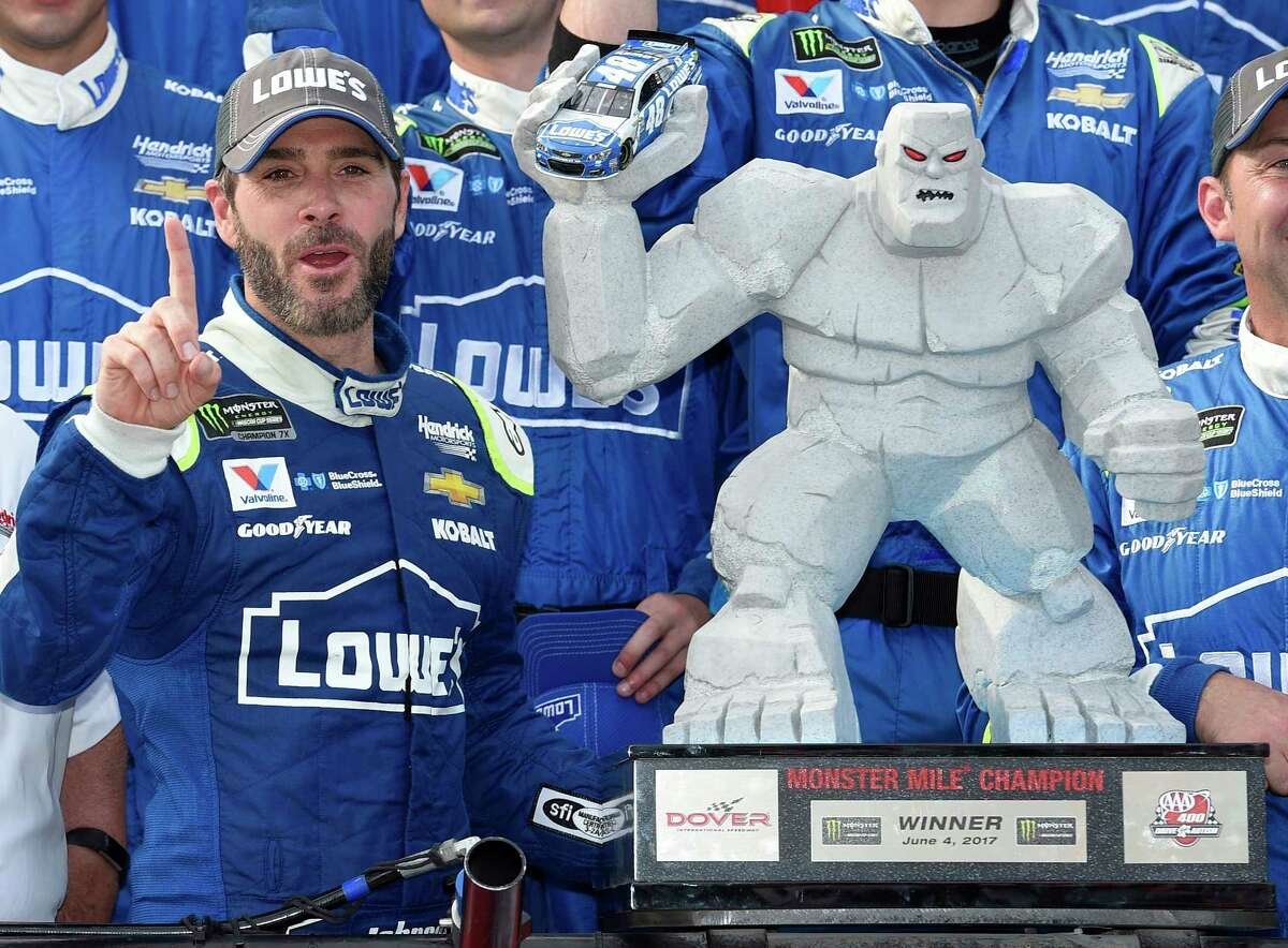 Jimmie Johnson, left, poses with the trophy in Victory Lane after he won a NASCAR Cup series auto race, Sunday, June 4, 2017, at Dover International Speedway in Dover, Del. (AP Photo/Nick Wass) ORG XMIT: DOV113
