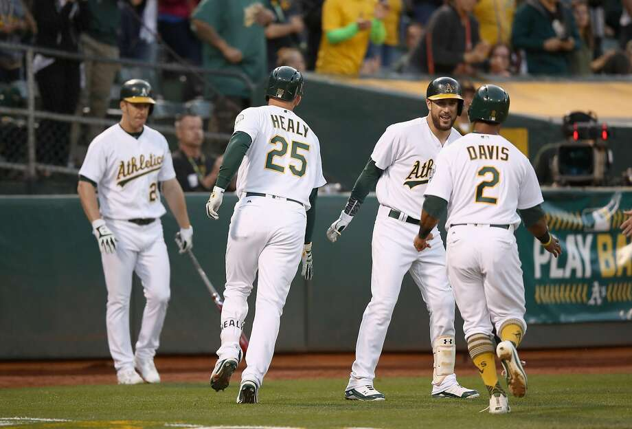 Ryon Healy of the Oakland Athletics and Khris Davis are congratulated by Trevor Plouffe after Healy hit a two-run home run in the fourth inning against the Toronto Blue Jays at Oakland Alameda Coliseum on June 5, 2017 in Oakland, California. Photo: Ezra Shaw, Getty Images