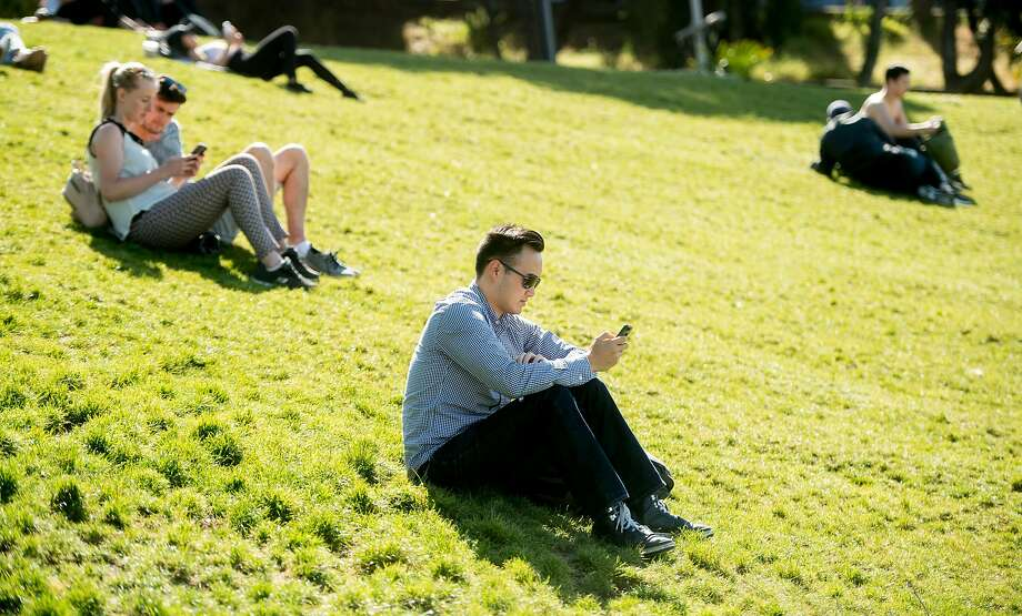 Patrick Ngo and other Mission Dolores Park visitors use cell phones on Monday, June 5, 2017. The park offers a free San Francisco WiFi hotspot. Photo: Noah Berger, Special To The Chronicle