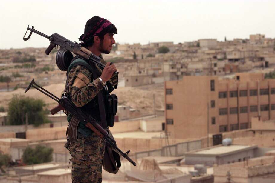 """FILE - In this Sunday, April 30, 2017, file photo, provided by the Syria Democratic Forces (SDF), shows a fighter from the SDF carrying weapons as he looks toward the northern town of Tabqa, Syria. A U.S. military official says the offensive against the Islamic State group's de facto capital, Raqqa """"will be long and difficult."""" Lt. Gen. Steve Townsend, the top U.S. commander in Iraq, says the assault by the Syrian Democratic Forces will deliver a decisive blow to the idea of IS """"as a physical caliphate."""" The Kurdish-led force launched an offensive to capture Raqqa on Tuesday.(Syrian Democratic Forces, via AP, File) Photo: Uncredited, HONS / Associated Press / Syrian Democratic Forces"""
