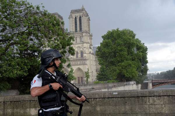 A French police officer holds a weapon as he stands near the entrance of Notre-Dame cathedral in Paris on June 6, 2017.  Anti-terrorist prosecutors have opened a probe after police shot and injured a man who had tried to attack an officer with a hammer outside Notre Dame cathedral. The officer was slightly injured in the attack outside the world-famous landmark in central Paris. One of his colleagues responded by shooting him, wounding the attacker, whose motives were not immediately known, according to a police source.