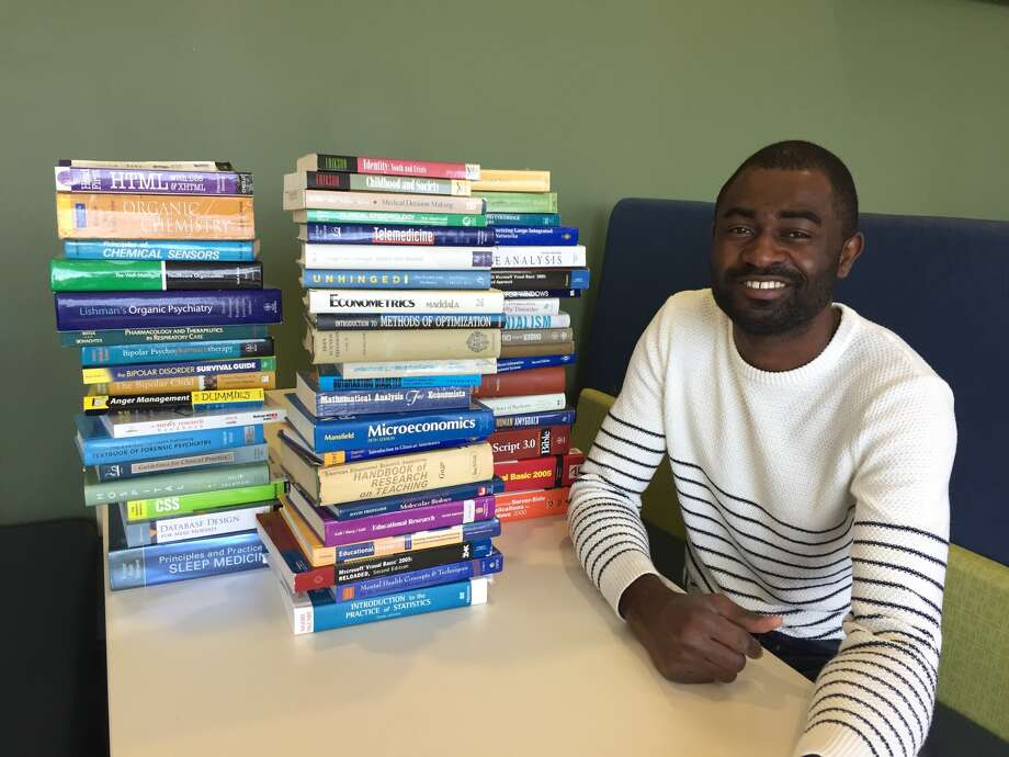 Graduate student Philip Alabi poses next to stacks of donated textbooks that have been collected through his non-profit organization EFIWE. Photo: Julia Biggs • Intelligencer