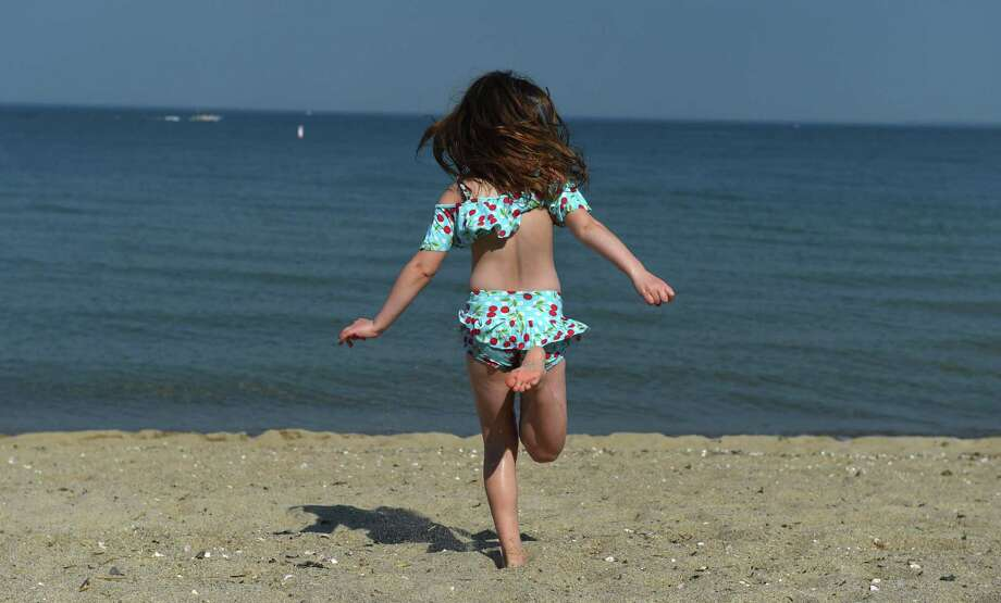 A girl runs to the water at Tods Point Beach on the Long Island Sound in Old Greenwich, Connecticut on May 18, 2017. CT DEEP says that even beach-goers are sound stakeholders and that the department wants to hear from them. Photo: TIMOTHY A. CLARY / AFP /Getty Images / AFP or licensors