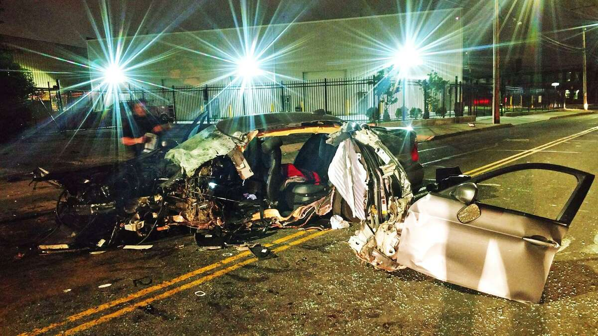 The wreckage of a BMW sedan sits in the road where it crashed early Tuesday morning on an arterial street in Bridgeport, Conn., June 6, 2017 .
