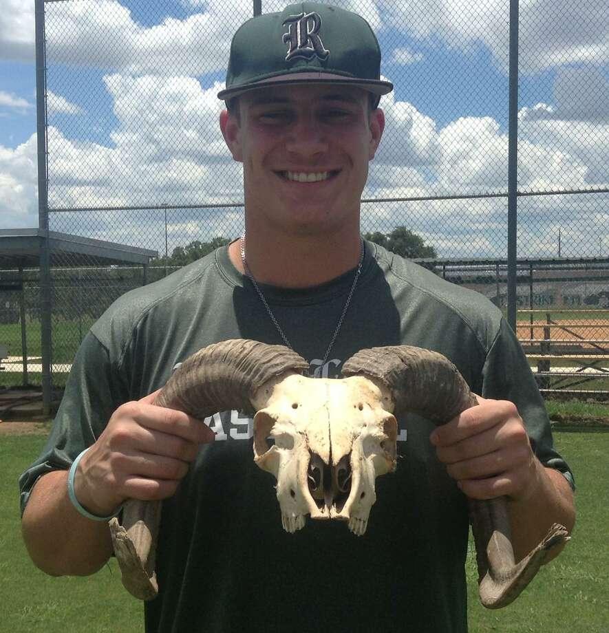 Reagan senior designated hitter Kyle Brookover shows off the Rattlers' good-luck charm for the playoffs -- a ram's skull. Photo: Adam Zuvanich / San Antonio Express-News