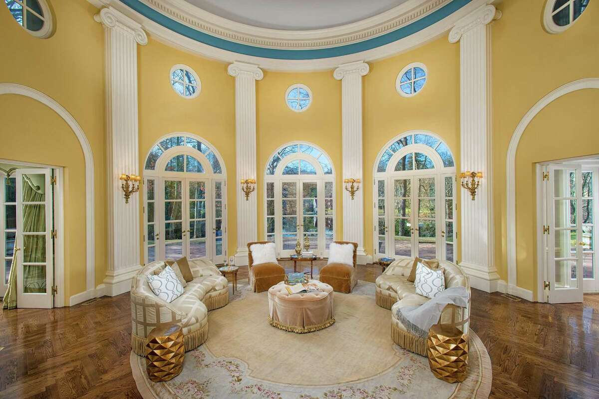 The three-story rotunda has a copper dome, fluted ionic columns, decorative molding, and Palladium windows with French doors to the terrace that looks over a pond on the Silvermine River.