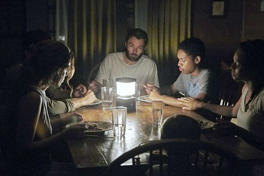 "Riley Keough (clockwise from left), Christopher Abbott as the intruder, Joel Edgerton, Kelvin Harrison Jr., Carmen Ejogo and Griffin Robert Faulkner in ""It Comes at Night,"" in which a family is holed up in a house after a vague apocalypse. Photo: Eric McNatt, A24 Films"