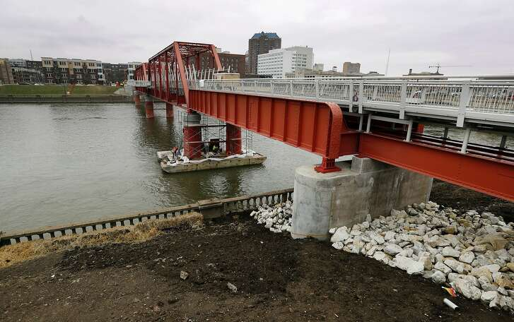 In this March 28, 2017, photo, the Red Bridge pedestrian bridge is seen over the Des Moines River in Des Moines, Iowa. A little more than a decade after it was restored, crews went back to the site with a crane to hoist the span more than 4 feet higher, at a cost of $3 million, after experts concluded that the river's flooding risk was double the previous estimates. (AP Photo/Charlie Neibergall)