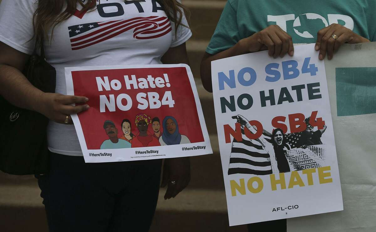 """Protesters chant and hold signs about Senate Bill 4 Thursday during an announcement about the city's lawsuit. Bexar County commissioners voted 4-1 Tuesday to join the San Antonio lawsuit filed last week challenging the constitutionality of the state's recently passed """"sanctuary cities"""" law."""