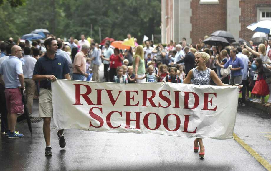 Teachers hold a banner as students follow behind during the Parade of Learners on the first day of school at Riverside School. Photo: Tyler Sizemore / Hearst Connecticut Media / Greenwich Time
