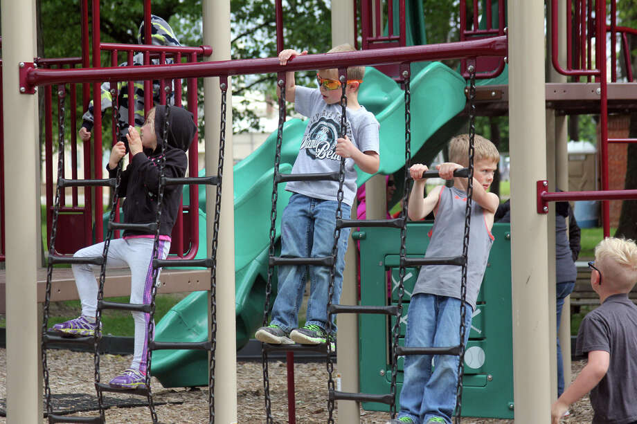 From left, Bad Axe kindergarten students Abigail Vahovick, Dylan Bairski-Peters and Collin VanValkenburgh hang around at Bad Axe City Park on Tuesday.