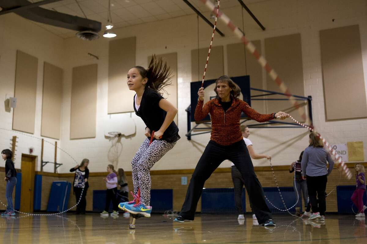 BRITTNEY LOHMILLER | blohmiller@mdn.net With help from a parent volunteer Eastlawn Elementary gym teacher Diane Sugnet spins two jump ropes while fourth-grader Mali Prany jumps double Dutch with a pogo stick inside the school's gym on Thursday morning. Sugnet opens the school's gym on Monday's, Thursday's and Friday's for approximately 40 students to come and jump rope before school for jump rope team practice. Former Parkdale gym teacher Ernie Carter started the jumping rope team and when he retired, 10 years ago, Sugnet took over the team and when Parkdale closed she brought the team to Eastlawn.