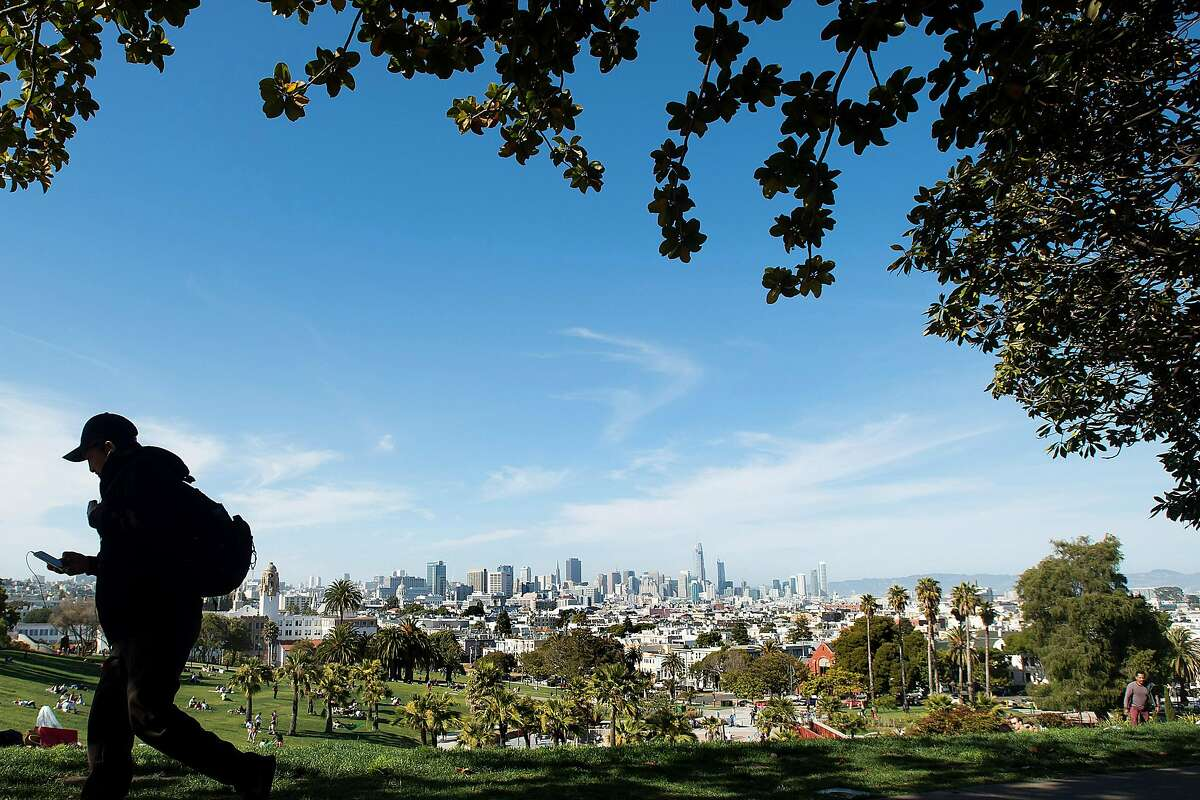 A man checks his phone while walking past Mission Dolores Park on Monday, June 5, 2017. The park offers a free San Francisco WiFi hotspot.