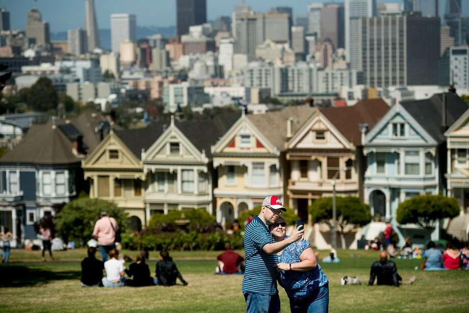 Katie and Aaron Smith take a photo while visiting Alamo Square Park on Monday, June 5, 2017. The park offers a free San Francisco WiFi hotspot. Photo: Noah Berger, Special To The Chronicle