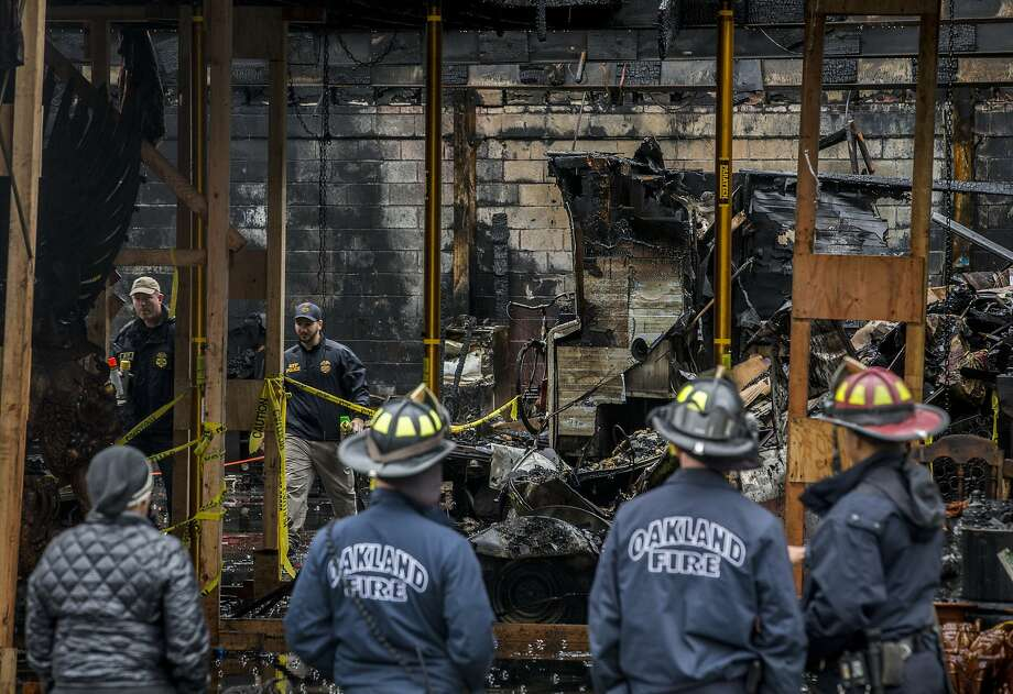 AFT police officials inspect the Ghost Ship warehouse from inside as Oakland firefighters investigate outside on Saturday, Dec. 10, 2016 in Oakland, Calif. 36 people were killed when a fire broke out on Dec. 2 at the Ghost Ship warehouse on 31st Avenue and International Boulevard in Oakland's Fruitvale neighborhood. As many as 100 people were inside attending a music performance. The blaze is now the deadliest structure fire in California since the 1906 earthquake and fire. Officials said the cause of ignition is still unknown and the building had no evidence of fire sprinklers. Photo: Santiago Mejia / The Chronicle 2016