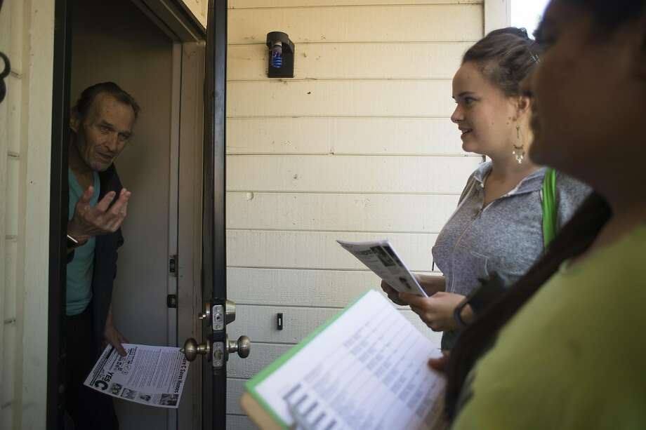 Canvassers Ana Lugo and Alyssa Glass-Kyes hand a pamphlet to Darryl Sismil during a special election to see if residents approve the measure to establish rent and eviction control in Santa Rosa on June 6, 2017. Photo: Brian L. Frank, Special To The Chronicle