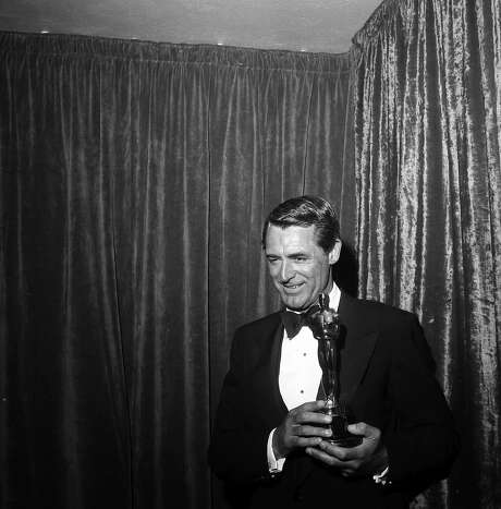 Cary Grant poses with an Oscar for Ingrid Bergman in Los Angeles, 1957. Photo: Earl Leaf, Getty Images