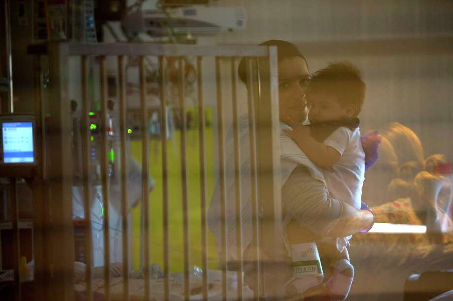 Seen through a glass window, Blanca Romero holds her three-month-old son, Sebastian, in his isolation room at Texas Children's Hospital, Tuesday, May 23, 2017, in Houston. Sebastian was born with Severe Combined Immunodeficiency Disease, commonly known as SCID, which was identified in his newborn screening. Photo: Mark Mulligan, Mark Mulligan / Houston Chronicle / 2017 Mark Mulligan / Houston Chronicle