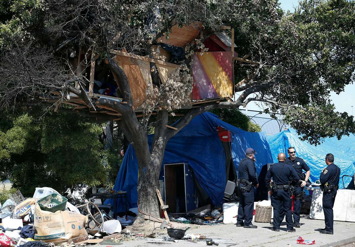 Oficers stand by below a tree house while a public works crew removes discarded belongings and debris in June from a homeless encampment on East 12th Street in Oakland.