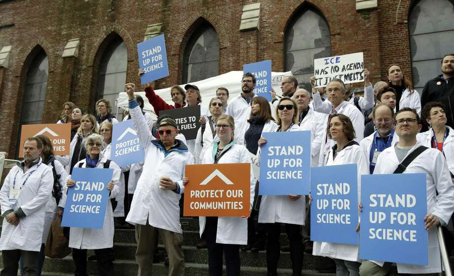FILE - In this Dec. 13, 2016 file photo, scientists hold signs during a rally in conjunction with the American Geophysical Union's fall meeting in San Francisco. The rally was to call attention to what scientist believe is unwarranted attacks by the incoming Trump administration against scientists advocating for the issue of climate change and its impact. Vowing to keep the United States on track to meet its emissions-cutting target even without the U.S. government's support, more than a dozen governors representing nearly 40 percent of the U.S. economy by Tuesday, June 6, 2017, had pledged themselves to stay in the climate-change fight despite the Trump administration's withdrawal from the Paris climate accords last week. (AP Photo/Marcio Jose Sanchez, File) Photo: Marcio Jose Sanchez, STF / Associated Press / Copyright 2017 The Associated Press. All rights reserved.