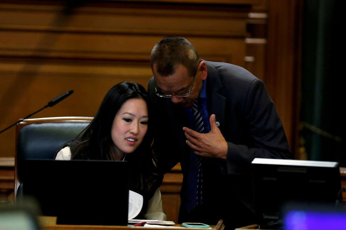 Supervisors Katy Tang (left) and Norman Yee speak before a Board of Supervisors meeting at City Hall in San Francisco, California, on Tuesday, Dec. 15, 2015.