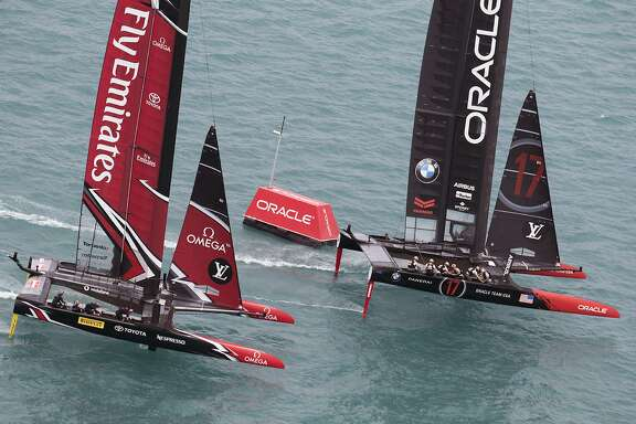 In this photo provided by the America's Cup Event Authority, Emirates Team New Zealand and Oracle Team USA compete during America's Cup qualifying on the Great Sound in Bermuda on Saturday, June 3, 2017.  (Gilles Martin-Raget/ACEA via AP)