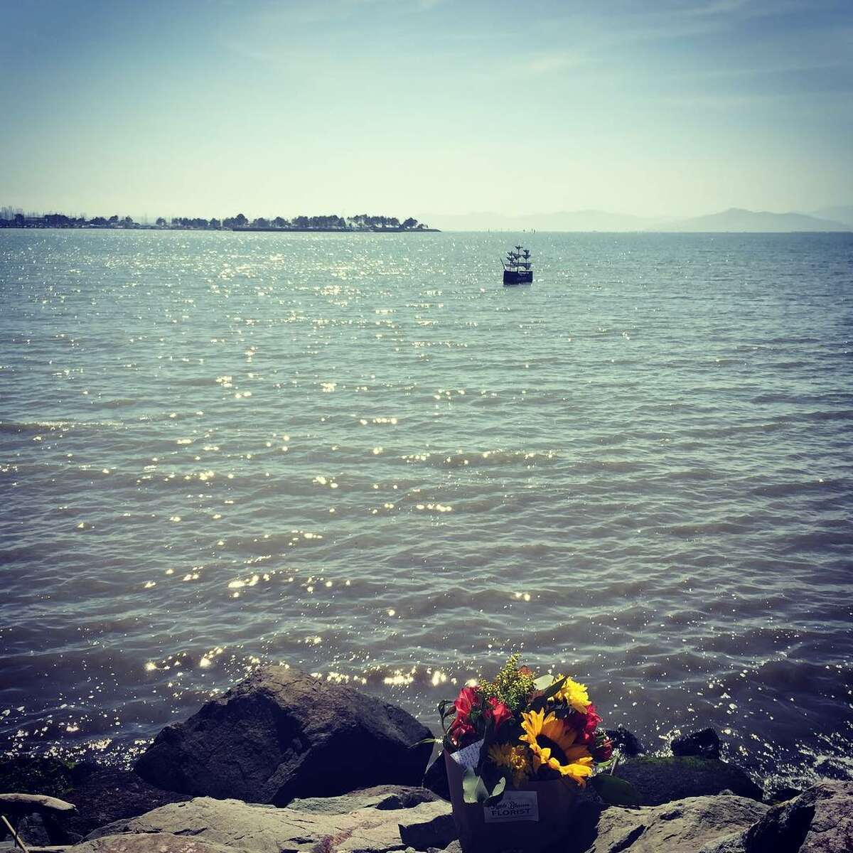 A bouquet of flowers are seen along the shore of Emeryville, near an art piece created by Chris Edwards.