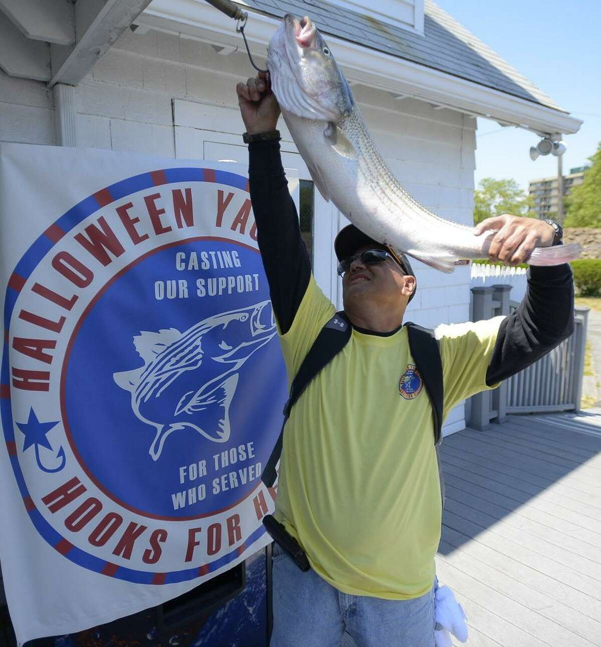 FILE - Newly retired, after 38 years of service, U.S. Army Staff Sergeant Steven Betancourt, who served in combat and was wounded in the Iraq war, weighs in a 14 lbs Striped Bass during the Hooks for Heroes Charity Fishing Tournament at the Halloween Yacht Club in Stamford, Conn. on Saturday, June 25, 2016.